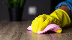 Mão com luva e esponja limpando a mesa da casa