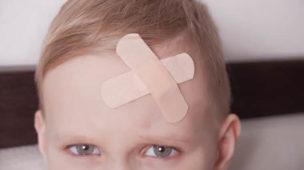 menino com concussão na cabeça, machucado, curativo