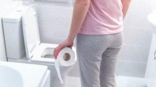 mulher segurando papel higiênico indo até o vaso sanitário
